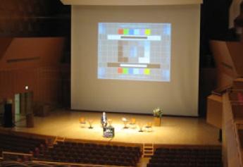 大型スクリーンとプロジェクターを使用した講演会の様子